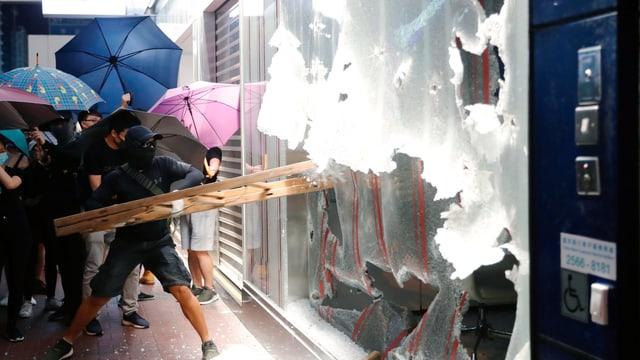 Demonstrant schlägt Schaufenster ein