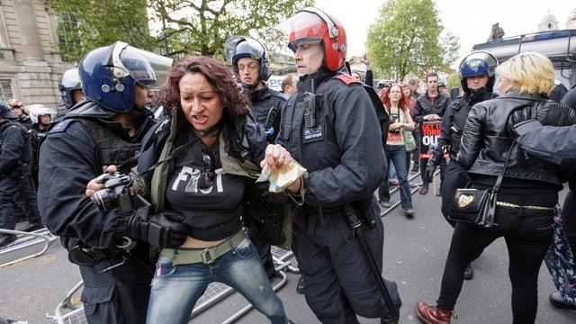 Polizisten nehmen eine Demonstrantin fest.
