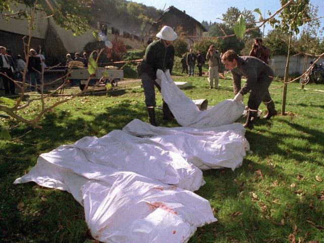 Polizisten tragen mit Tüchern bedeckte Leichen ins Freie.