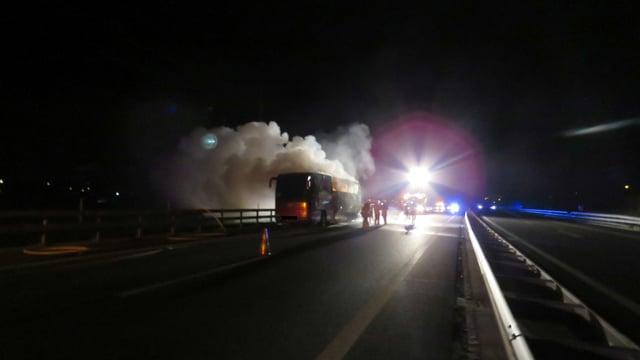 Der Carbrand ist gelöscht, aus dem Fahrzeug quillt Rauch. Im Hintergrund das helle Licht eines Scheinwerfers.