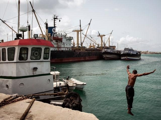 Ein Schwarzer springt im Hafen von der Mauer ins Wasser.
