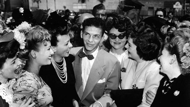 Frank Sinatra jung und von Frauen umzingelt.