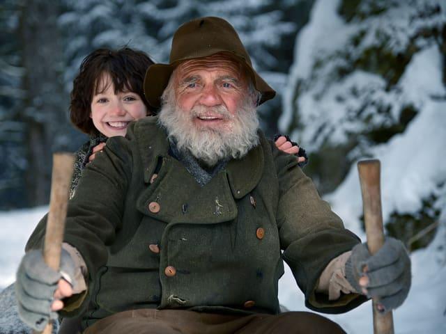 Eine Filmszene aus «Heidi»: Das Mädchen sitzt auf dem Schlitten mit dem Alpöhi (Bruno Ganz).