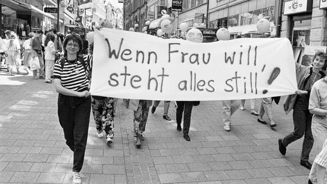 Zwei Frauen tragen ein Banner mit der Aufschrift: «Wenn Frau will, steht alles still.»