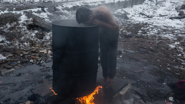 Junger Mann mit nacktem Oberkörper und barfuss wäscht sich draussen in der Kälte mit warmen Wasser aus einer Tonne, die über dem offenen Feuer erhitzt wird
