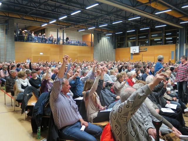 Menschen in Halle, halten Hände in die Höhe.