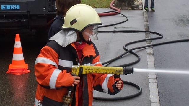 Bub in voller Feuerwehrmontur betätigt den Schlauch.