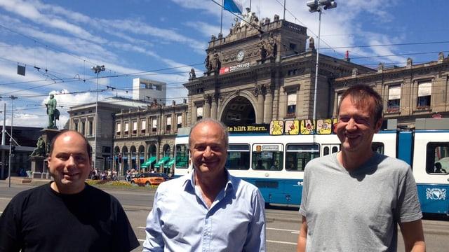Die drei Männer stehen am Verkehrskonten Bahnhofplatz, im Hintergrund der Zürcher Hauptbahnhof.