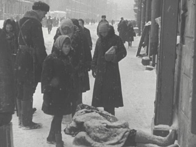 Menschengruppe steht auf schneebedeckter Strasse um eine Leiche.