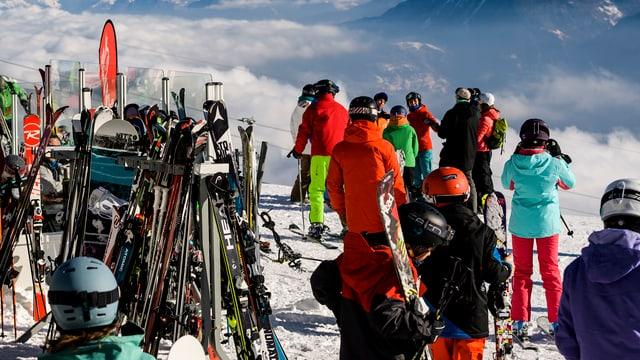 Situaziun a l'ur d'ina pista da skis cun blers uffants e creschids sin skis ed in deposit da skis.
