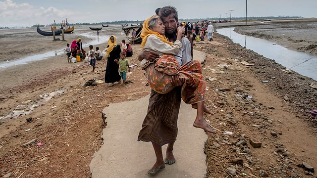 Mann trägt eine ältere Frau im Niemandsland, hinter ihm weitere Menschen.