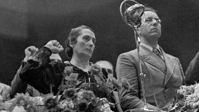 Eine Frau reckt kämpferisch die Faust in die Höhe, neben ihr steht ein Mann, beide schauen ernst an der Kamera vorbei