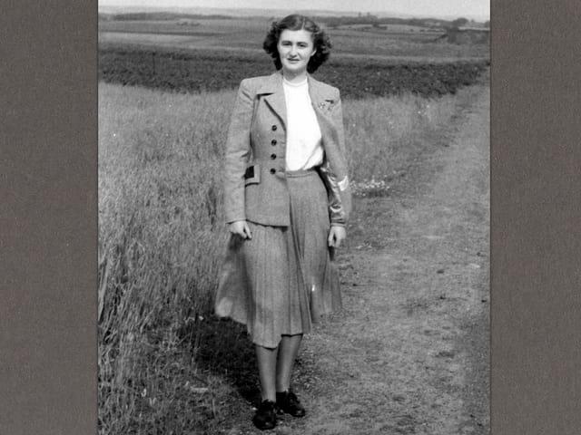 Die junge June steht auf einem Feld und schaut in die Kamera