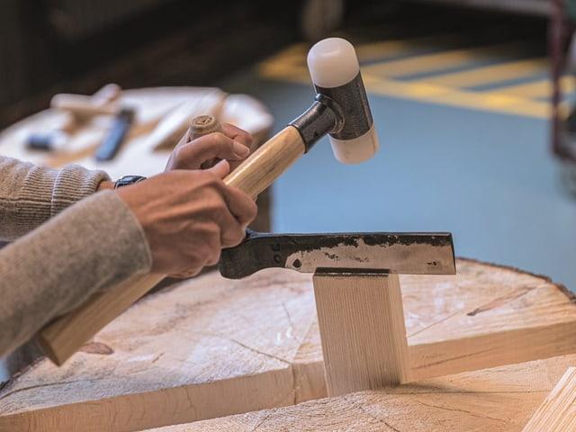Ein Foto einer Person, die mit Holz arbeitet: In der Schindelwerkstatt legt das Publikum selber Hand an.