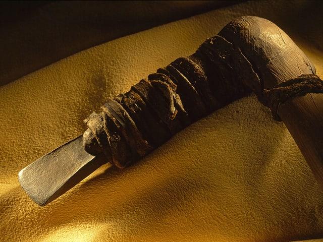 Eine steinzetiliche Axt auf einem gelben Tuch