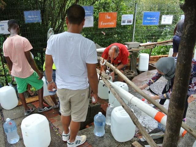 Männer und Frauen füllen Wasserkanister.