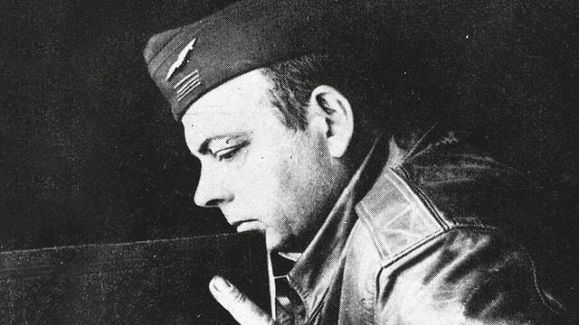 Schwarzeweissaufnahme: Saint-Eyupéry in Militärpiloten-Uniform hält ein grosses Buch.
