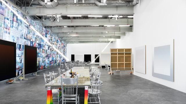 Ein grosser Raum: In der Mitte eine Tafel, links davon ein Vorhang mit Fotos.