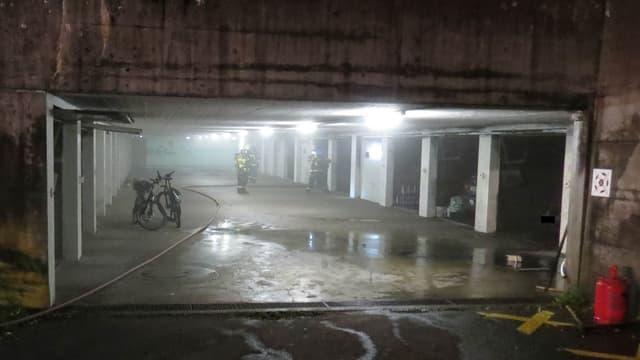 Mehrere Feuerwehrleute in einer Garage.