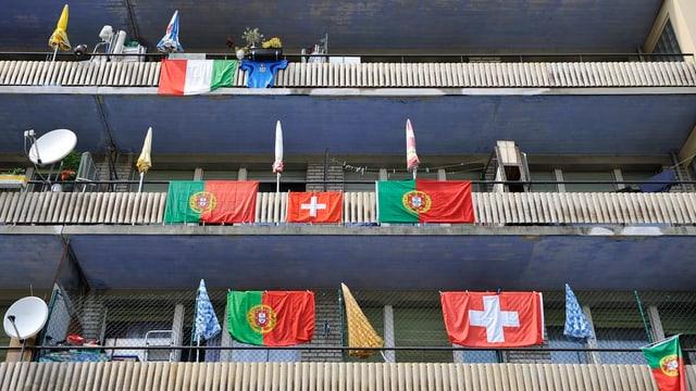 Eine mehrstöckiges Haus mit Balkonen, an denen italienische, portugiesische und Schweizer Fahnen wehen.