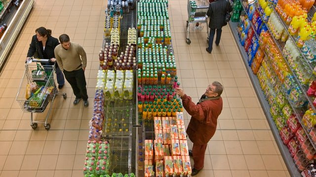 Getränkeregale in einem Supermarkt, ein Paar mit einem Einkaufswagen, ein Mann nimmt eine Flasche aus dem Regal.