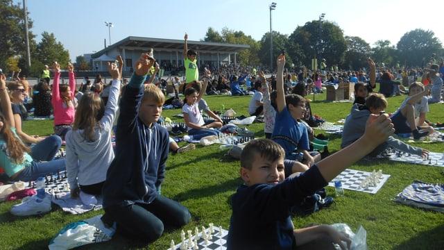 Kinder sitzen am Boden und strecken einen Arm in die Höhe, als wollten sie sich im Unterricht melden.