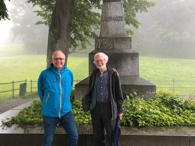 Marcel Hähni und Urs Bosshard stehen vor dem steinernen Schlachtdenkmal auf dem Stoss (AR).