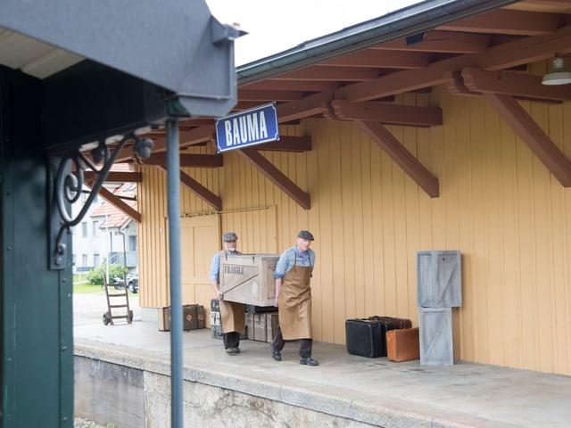 Zwei Männer tragen Holzkiste am Bahnhof Bauma