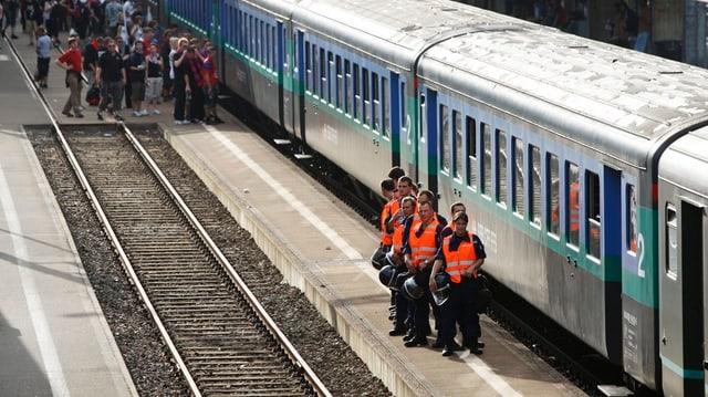 Sicherheitsleute vor einem Zug, hinten Fussballfans