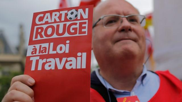 Ein Gewerkschafter hält eine rote Karte in die Kamera, darauf steht: «Carton Rouge à la Loi Travail».