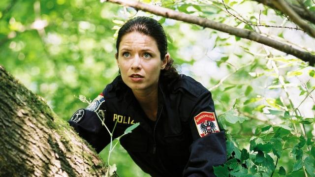 Eine Frau in Uniform versteckt sich hinter einem Baum.