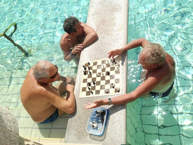 Drei Männer stehen im Wasser und spielen Schach.