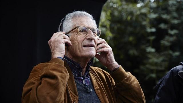 Seitenansicht, man sieht nur den Oberkörper. Ein älterer Mann mit Brille hält sich einen Kopfhörer an die Ohren und schaut lächelnd in die Ferne.