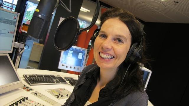 Eine Radiojournalistin mit Kopfhörer im Studio