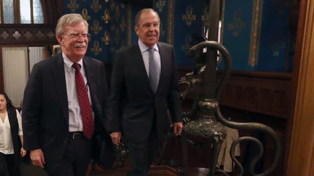 John Bolton und Sergei Lavrov gehen über einen Teppich