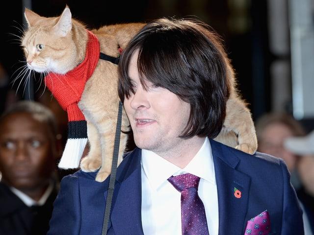 James Bowen und Katze Bob. DIe Katze sitzt auf seienr Schulter