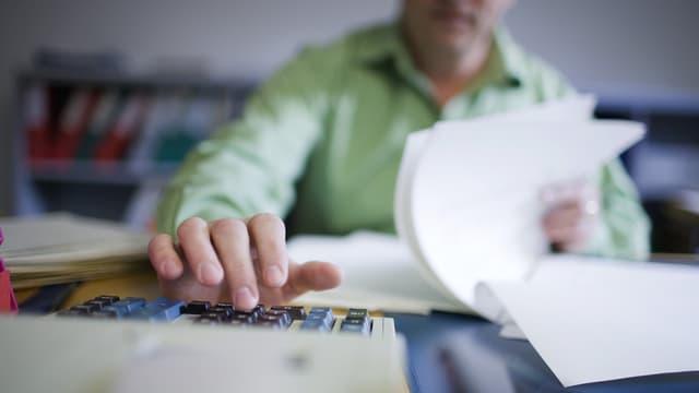 Mann blättert in Unterlagen und tippt auf einem Rechner herum