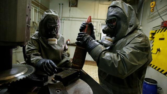 Zwei Männer in Schutzanzügen bei der Vernichtung von C-Waffen.