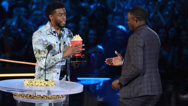 Zwei Männer, die sich einen Pocpcornbecher mti goldenem Popcorn überreichen.