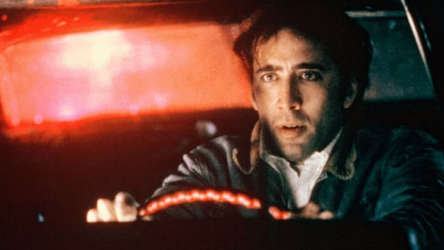 Ein Mann sitzt hinter dem Steuer eines Wagens.