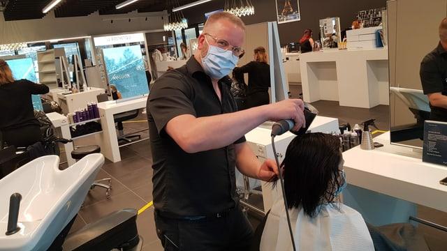 Ein Mann mit blauem Mundschutz föhnt einer Kundin die Haare.