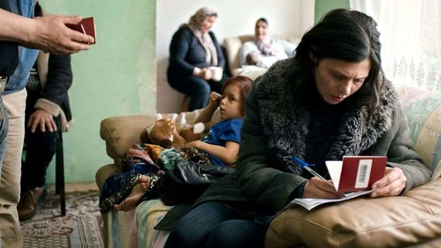 Marija schreibt Tagebuch in einem Wohnzimmer, hinter ihr zwei Frauen und ein Kind.