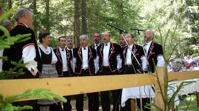 Jodlerchörli im Wald hinter Holzzaun. Mittels mehrer Mikrophone wird ihr Gesang aufgezeichnet.