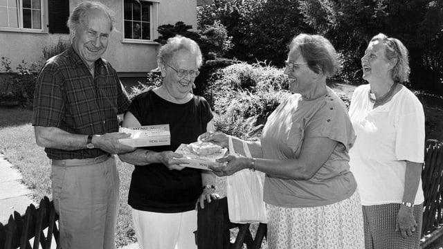 Schwarz-Weiss-Fotografie mit einer Gruppe von lachenden Menschen.