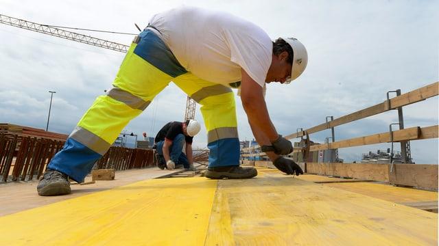 Bauarbeiter auf einer gelben Holzplatte. Er bückt sich.