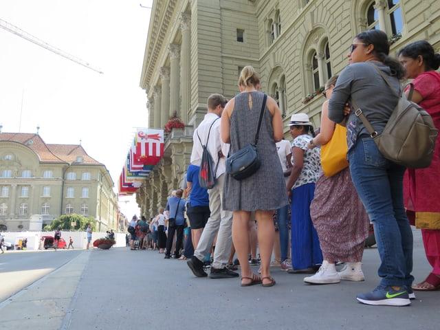 Menschen stehen vor dem Bundeshaus Schlange. Sie warten auf Einlass.