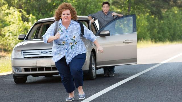 Melissa McCarthy rennt auf einer Landstrasse. Im Hintergrund ein Auto.