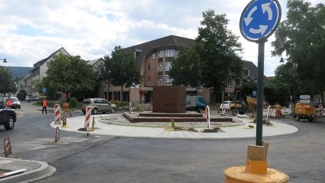 Ein verkehrskreisel, an dem gebaut wird. Im Vordergrund steht das Strassenschild, das auf den Kreisel hinweist.