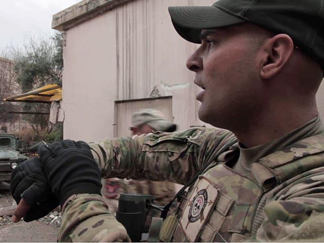 Offizier Ahmad schaut auf seine Uhr.