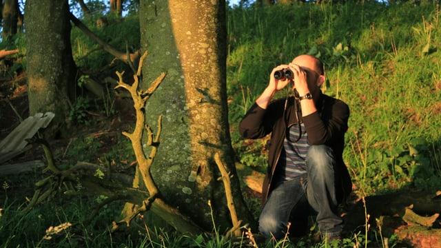 Andrew Bond mit Feldstecher im Wald
